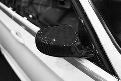 Carbon Right side Car mirror with reflection of a modern car. Car exterior details. Black and white Stock Image