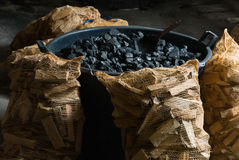 Carbon and wood. Bucket of carbon and sacks of pieces of wood royalty free stock image