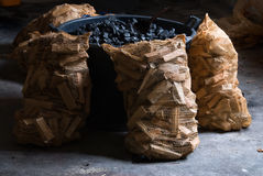 Carbon and wood. Bucket of carbon and sacks of pieces of wood Stock Image