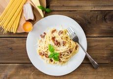 carbonara日光拍的意大利面食照片 意粉用烟肉和帕尔马干酪和成份 库存照片
