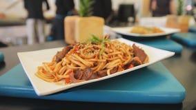 Carbonara cocinado en una placa en una tabla, cierre de los espaguetis para arriba Cámara de enfoque Alimento tradicional Tallari almacen de metraje de vídeo
