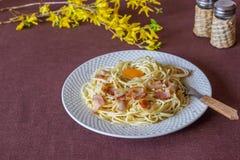Carbonara de las pastas Flores en el fondo Alimento italiano imagenes de archivo