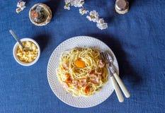 Carbonara de las pastas Flores en el fondo Alimento italiano fotografía de archivo