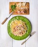 Carbonara de los espaguetis en placa verde en el fondo de madera blanco Fotos de archivo libres de regalías