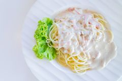Carbonara de los espaguetis o salsa cremosa blanca con la porción del tocino en la placa blanca imagen de archivo
