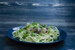 Carbonara della pasta con carne di maiale, erbe fresche, spruzzate con sesamo sopra un piatto blu Priorit? bassa di legno scura V fotografie stock