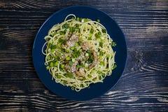 Carbonara della pasta con carne di maiale, erbe fresche, spruzzate con sesamo sopra un piatto blu Priorit? bassa di legno scura V fotografia stock