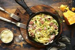 Carbonara italiano tradicional de los espaguetis del plato con tocino en un cre Imágenes de archivo libres de regalías