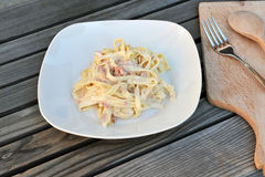 Carbonara. Carbonara pasta dish on a white plate with fork and wooden spoon on a cutting board next to it Stock Photo