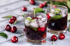 Carbonated chilled drink from sweet cherry. On the light wooden background Royalty Free Stock Photography