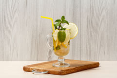 Carbonated lemonade with lemon slices and mint on an wooden cutt Stock Images