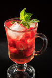 Carbonated lemonade with strawberry slices and mint. On the black background. Cold beverage for hot summer day Royalty Free Stock Photo