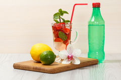 Carbonated lemonade with strawberry slices and mint on an wooden. Cutting board, Cold beverage for hot summer day Stock Photos