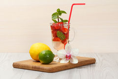Carbonated lemonade with strawberry slices and mint on an wooden. Cutting board, Cold beverage for hot summer day Stock Images