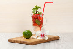 Carbonated lemonade with strawberry slices and mint on an wooden. Cutting board, Cold beverage for hot summer day Stock Photography