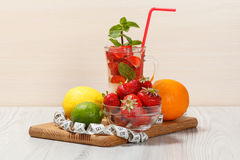 Carbonated lemonade with strawberry slices and mint on an wooden. Cutting board, Cold beverage for hot summer day Royalty Free Stock Photography