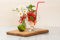 Carbonated lemonade with strawberry slices and mint on an wooden. Cutting board, Cold beverage for hot summer day Stock Image