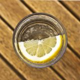 Carbonated soda water with lemon in a glass with bubbles on a br royalty free stock photography