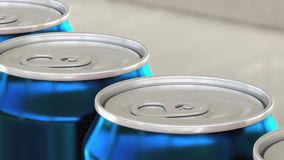 Carbonated soft drink or beer production line. Blue aluminum cans on industrial conveyor. Recycling ecologic packaging stock photography