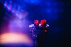 Carbone per Shisha sulla ciotola di rosso caldo su un fondo blu Fotografia Stock Libera da Diritti