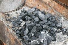Carbone in stufa locale in campagna immagine stock