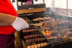 Carbones de Person Cooking Kebabs Over Hot en parrilla fotografía de archivo libre de regalías