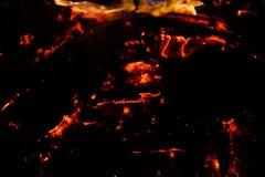 Carbones que arden en un fondo negro imágenes de archivo libres de regalías