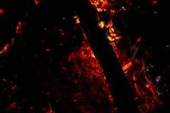 Carbones que arden en un fondo negro imagen de archivo libre de regalías