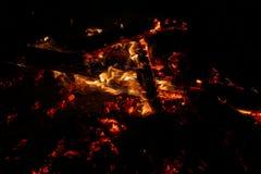 Carbones que arden en un fondo negro imagenes de archivo