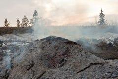 Carbones y cenizas que brillan intensamente y que fuman Imagen de archivo libre de regalías