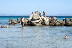 Carbonia, Italy - August 10: Unidentified people relax on a rock Stock Photo