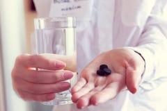 Carbono y agua activados en las manos de un doctor Fotografía de archivo