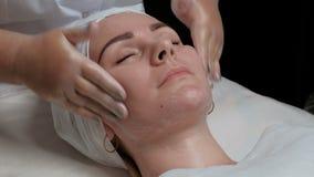 Carboxytherapy Las manos del cosmetologist en el salón de belleza comienzan a limpiar la cara de una muchacha hermosa con los ojo almacen de metraje de vídeo