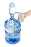 Carboy with drinking water, hand pump and a glass in a man's han Royalty Free Stock Image