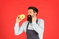 Carbs gluten diet. Bearded well groomed man in apron selling donuts. Donut food. Hipster baker hold donuts. Cheerful. Mood. Glazed donut. Baked goods. Sweets royalty free stock photography