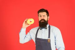 Carbs gluten diet. Bearded well groomed man in apron selling donuts. Donut food. Hipster baker hold donuts. Cheerful. Mood. Doughnut calories. Glazed donut stock photo