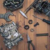 Carburatoren voor een motor van een auto met hulpmiddelen op houten lijst Stock Afbeelding