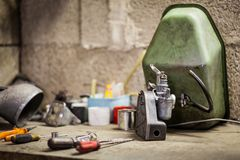 Carburetor with air filter and tank of old italian scooter. Small carburetor with air filter and fuel tank of old italian motorbike scooter on workbench with Stock Images