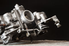 Carburetor on wooden surface. In black background Stock Photography