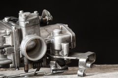 Carburetor on wooden surface. In black background Royalty Free Stock Photo