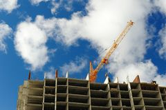 Carcass of new building and crane on blue cloudy sky copyspace Royalty Free Stock Photo