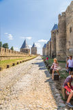 Carcassonne, France. Tourists under the walls of the medieval fortress. UNESCO list Stock Photo