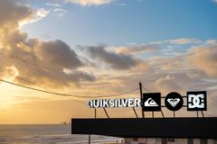 Carcavelos, Portugal - 12/27/18: Quiksilver brand at carcavelos beach. High contrast logo. Sunset, ocean waves, boat, surfers in the background royalty free stock images