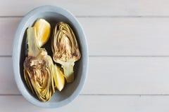 Carciofi arrostiti e limoni sul piatto Priorità bassa di legno bianca Questo prodotto ha uno di più alto antiossidante Fotografia Stock Libera da Diritti