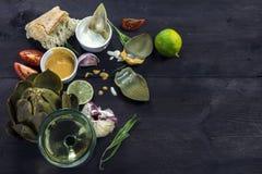 Carciofi con le immersioni, l'aglio, i pomodori, il limone, il pane ed il vino o Fotografie Stock