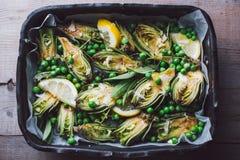 Carciofi freschi con prezzemolo ed i giovani fagioli in una teglia da forno Fotografia Stock