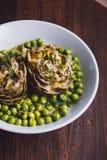 Carciofi freschi con prezzemolo ed i giovani fagioli in una teglia da forno, parmigiano nel fondo Immagine Stock
