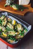 Carciofi freschi con prezzemolo ed i giovani fagioli in una teglia da forno, parmigiano nel fondo Fotografia Stock Libera da Diritti