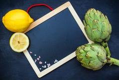 Carciofi freschi organici con il limone, fondo dello spazio della copia Immagine Stock Libera da Diritti