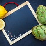 Carciofi freschi organici con il limone, fondo dello spazio della copia Immagini Stock Libere da Diritti